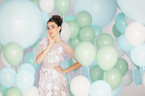 Beautiful woman in white dress surrounded by balloons